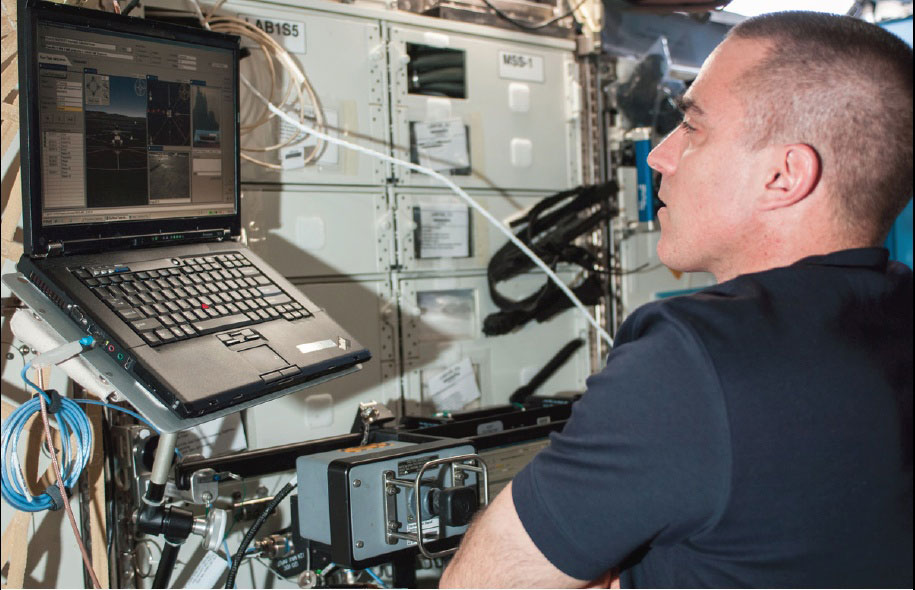 Photo credit: NASA. Chris Cassidy studies the Surface Telerobotics Workbench on the International Space Station to remotely operate the K10 rover on Earth at NASA's Ames Research Center in Moffett Field, Calif., in June 2013.