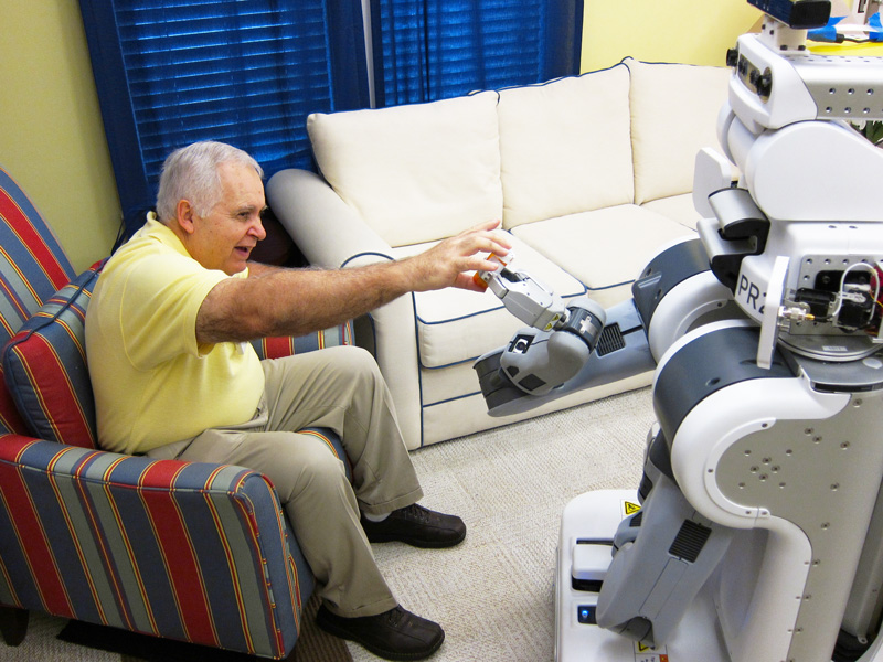 A robot hands a medication bottle to a person. Photo credit: Keith Bujak. Source: Georgia Tech News Center