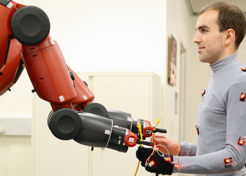 The Baxter robot hands off a cable to a human collaborator -- an example of a co-robot in action. Photo credit: Aaron Bestick, UC Berkeley.