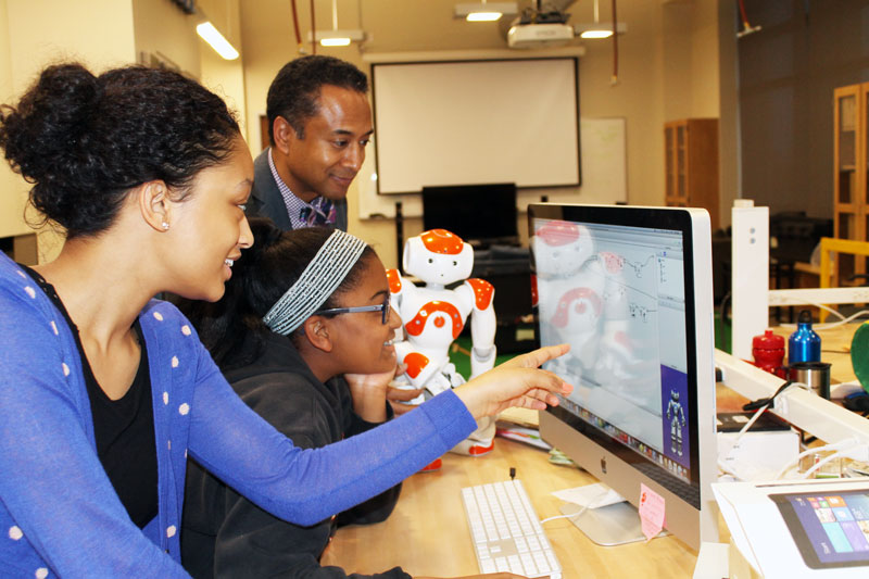 "Andrew Williams is shown with a couple of girls from the CompuGirls project. He says, ""In this project we're communicating to the girls that we're going to teach you how to use these technology tools with robotics to advance your community, better understand yourself and show that you do belong in technology and you have some valuable contributions you can make."""