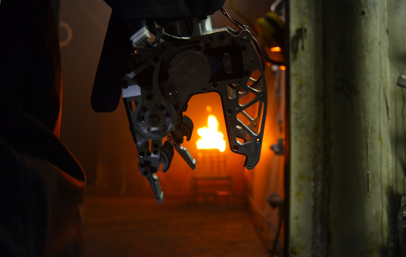"Firefighting robot: SAFFiR's hands are strong enough to grip and hold a firehouse blasting water. When operating the firehouse in wet conditions, the robot wore custom designed ""gloves"" to protect it from water damage. Source: Virginia Tech."