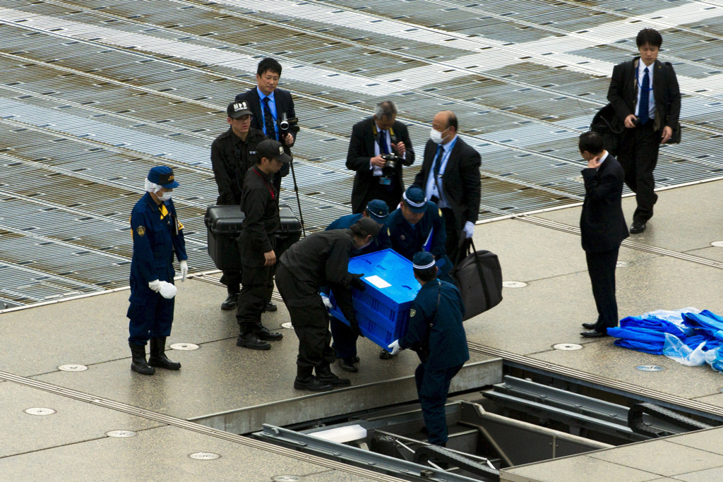 Japanese security members carry a box containing a drone that was landed on the roof of the Prime Minister's residence in Tokyo. Credit: Thomas Peter/Reuters