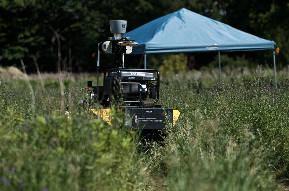 Grizzly RUV crossing dense vegetation and reaching autonomously one of its intermediate goal under the blue gazebo. The robot drove through different types of environments (ex.: indoor, outdoor, road, tall grass) using the same algorithms.  Photo credit: François Pomerleau - University of Toronto.