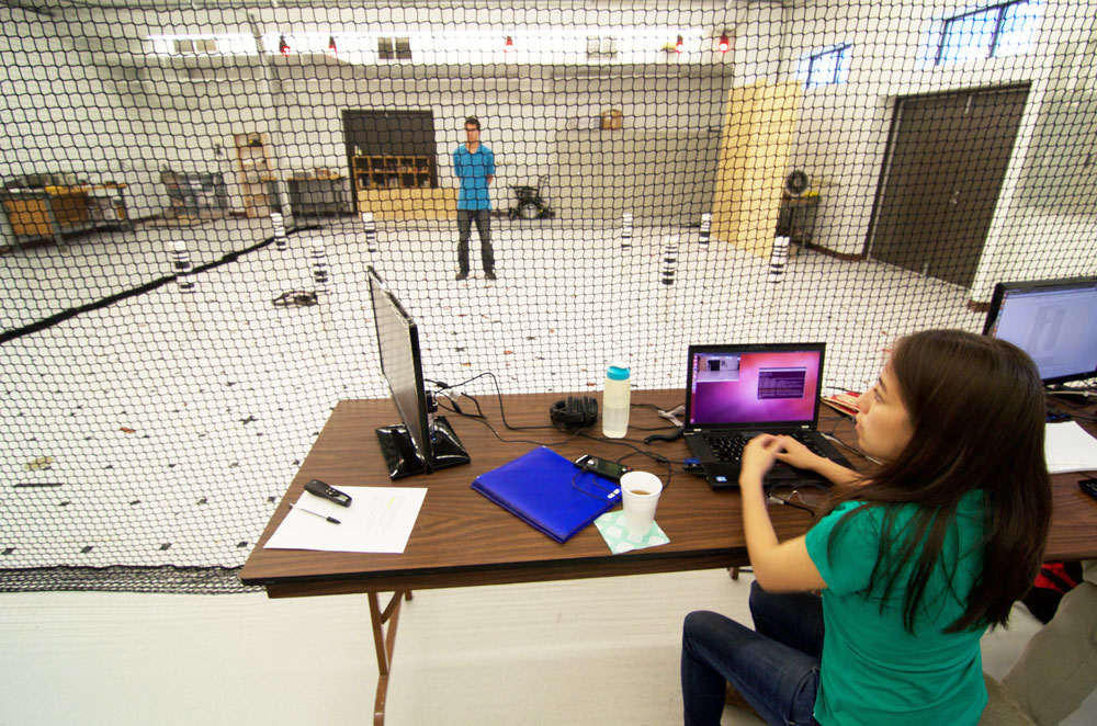 Karime Pereida Pérez launching a flight sequence for an Unmanned Aerial Vehicle (UAV). In the background, Rikky Duivenvoorden awaiting to apply interference forces on the UAV from inside the flying arena. Photo credit: François Pomerleau - University of Toronto.