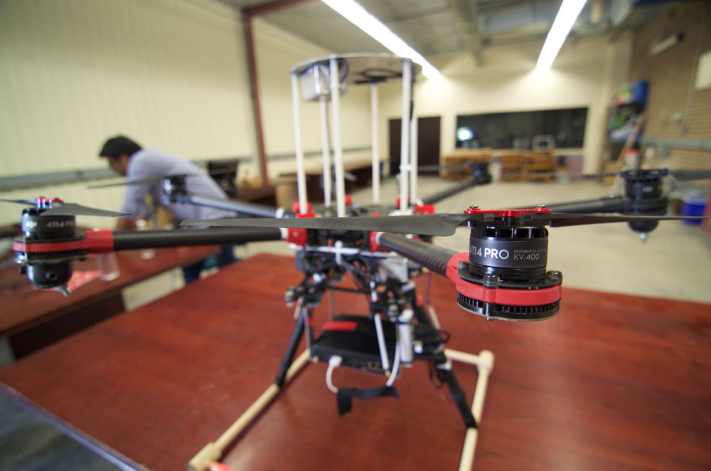 June 26, 2015 - The Waterloo Autonomous Vehicles Laboratory hexrotor drone, affectionately named Olga, sports three high-speed wide field-of-view cameras, which it uses to determine its own motion in unknown environments. Olga recently flew in Kelowna, BC at the NCFRN Field Trials, where it used the multi-camera cluster to construct maps of cliff faces and hiking trails, similar to those needed in mining and agriculture inspection applications. Photo credit: François Pomerleau - University of Toronto.