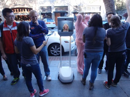 Using a BeamPro, Brianna Lempesis waits in line to buy an iPhone6s from the Apple Store in downtown Palo Alto. Photo: Suitable Technologies.