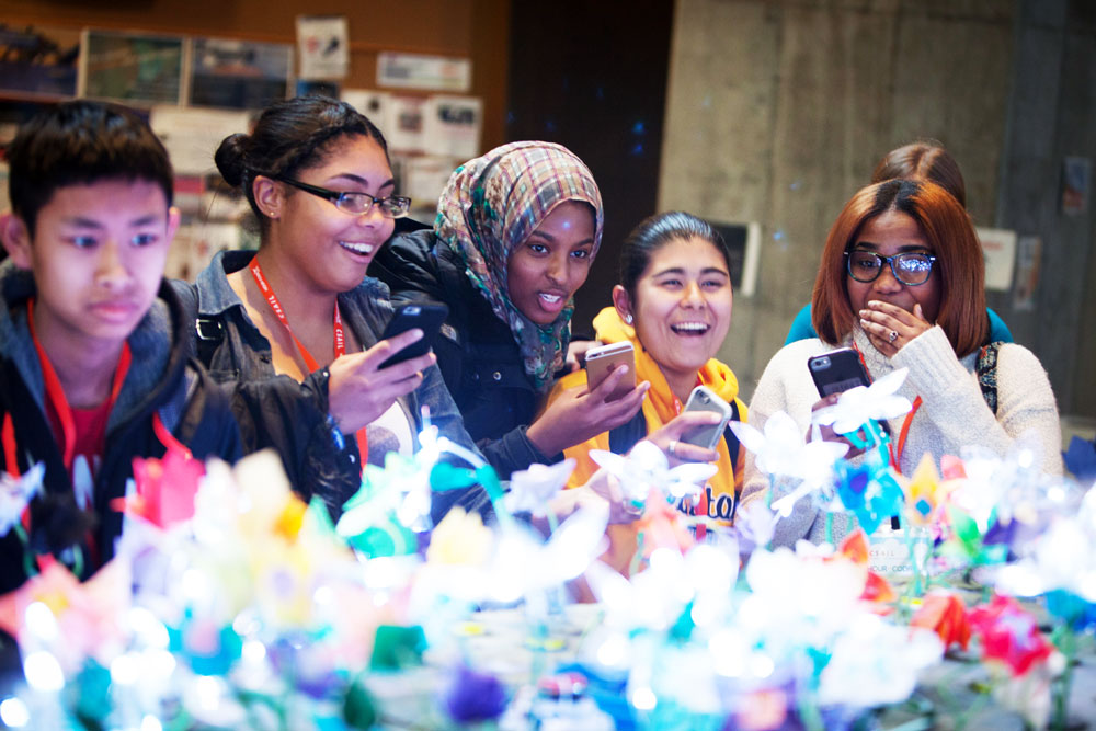 """Students watch CSAIL researchers show off a """"garden"""" made of dozens of distinct origami robots that move and change color to demonstrate complex programming algorithms. Photo: Jason Dorfman/CSAIL"""