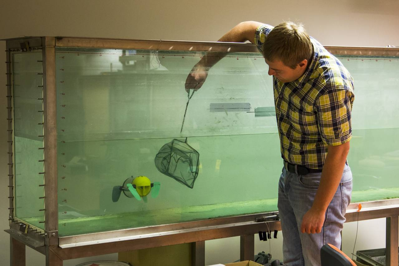 In this photo taken on Wednesday, Nov.  25, 2015, Taavi Salumae, designer of the U-CAT robot and researcher at the Biorobotics Centre at the Tallinn University of Technology, tests the U-CAT robot in an aquarium using a fish net in Tallinn, Estonia. The unique feature of the U-CAT, about the size of a vacuum cleaner, is four silicon flippers inspired by streamlined sea turtles' arms and legs. (AP Photo/Vitnija Saldava)