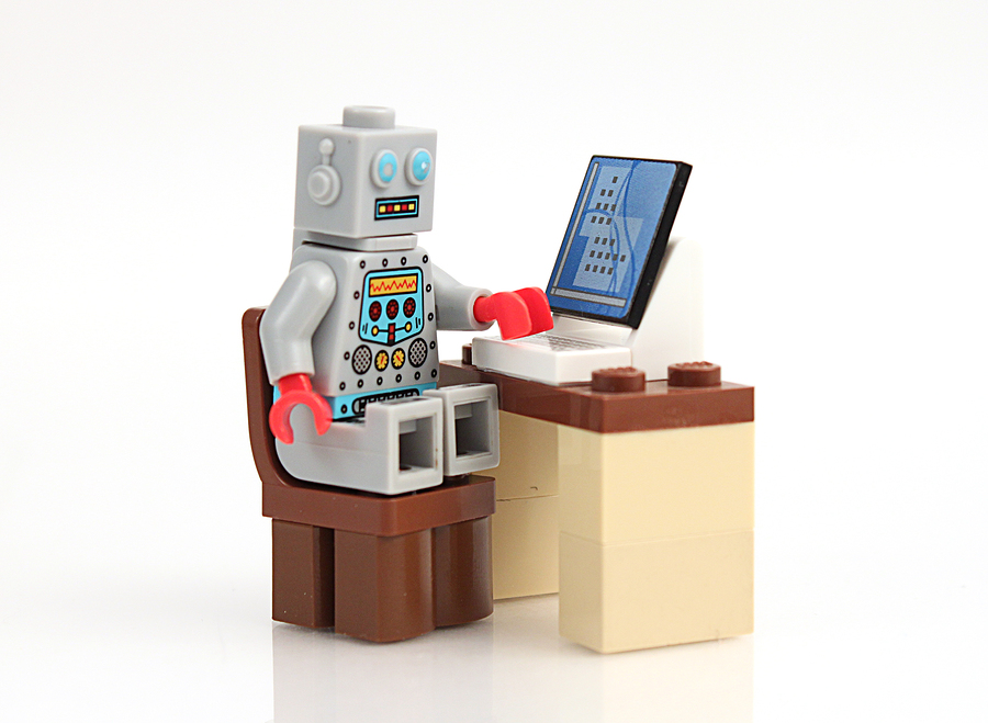 Studio shot of stack of Lego robot at computer. Photo: bigstockphoto