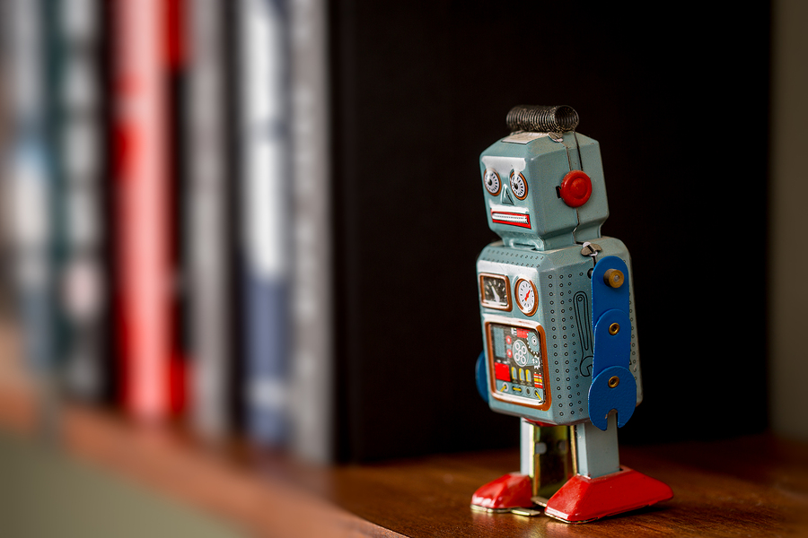 Retro tin toy robot standing on a wooden bookshelf
