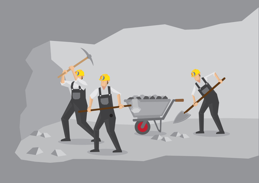 Cross section of underground tunnel showing miners at work with mining equipment.