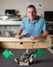 Georgia Tech Associate Professor Dan Goldman with the MuddyBot robot in the trackway where its motion was studied. Credit: John Toon, Georgia Tech
