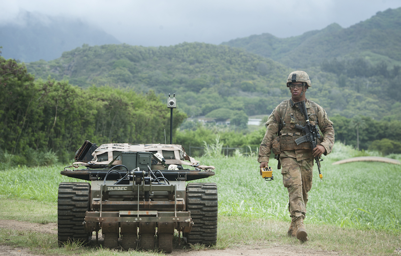 A U.S. Army Pacific Soldier moves down a road while controlling an unmanned vehicle as part of the Pacific Manned Unmanned – Initiative July 22, 2016, at Marine Corps Training Area Bellows, Hawaii. PACMAN-I provided an opportunity for Soldiers, partnered with organizations and agencies such as the Maneuver Center of Excellence and the U.S. Army Tank Automotive Research Development and Engineering Center, to test new technology in the field during practical exercises. (U.S. Air Force photo by Staff Sgt. Christopher Hubenthal)