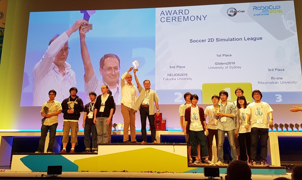 The author (centre podium, right) and Dr Obst (centre podium, left) claim the championship trophy at the 2016 RoboCup award ceremony in Leipzig, Germany. Credit: Natalia Kishigami