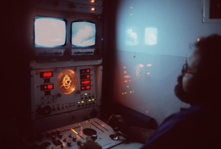 A technician controls the movement of the unmanned submersible Deep Drone from a control panel in the fleet tug USNS NARRAGANSETT (T-ATF 167). The submersible is being used to aid in the search for Korean Air Lines Flight 007. Photo from July 1984 All Hands Magazine.