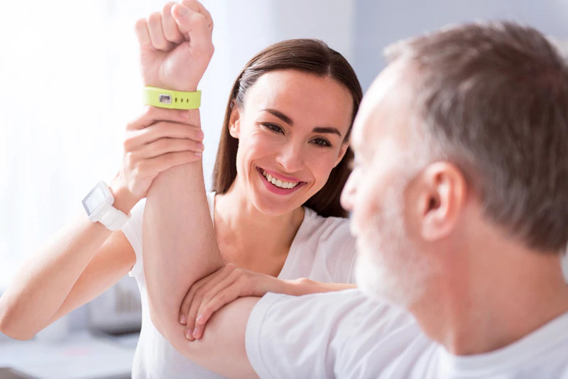 Therapist holding patient's arm, who is wearing an intelligent wereable device