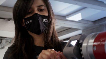 Film still showing Maria Vittoria Minniti working with a robot